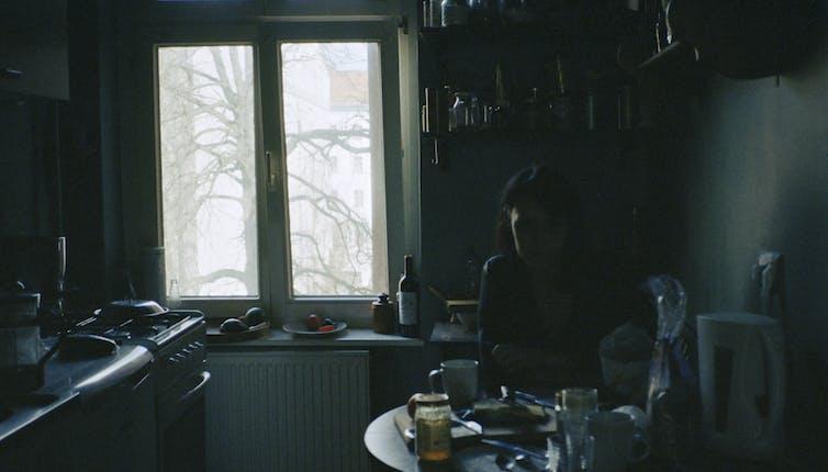 woman sitting in dark kitchen