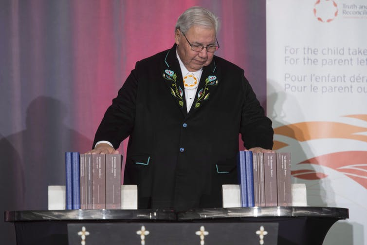 Murry Sinclair holds all the volumes of the TRC final report