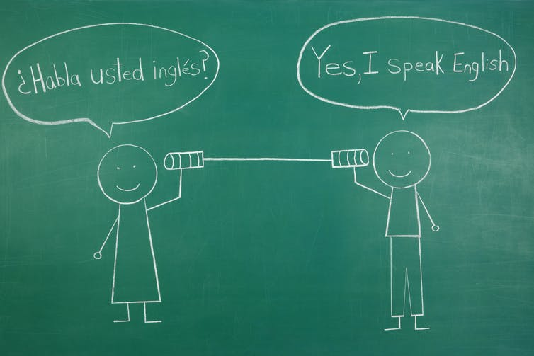 Two stick figures speak through a tin can in Spanish and English