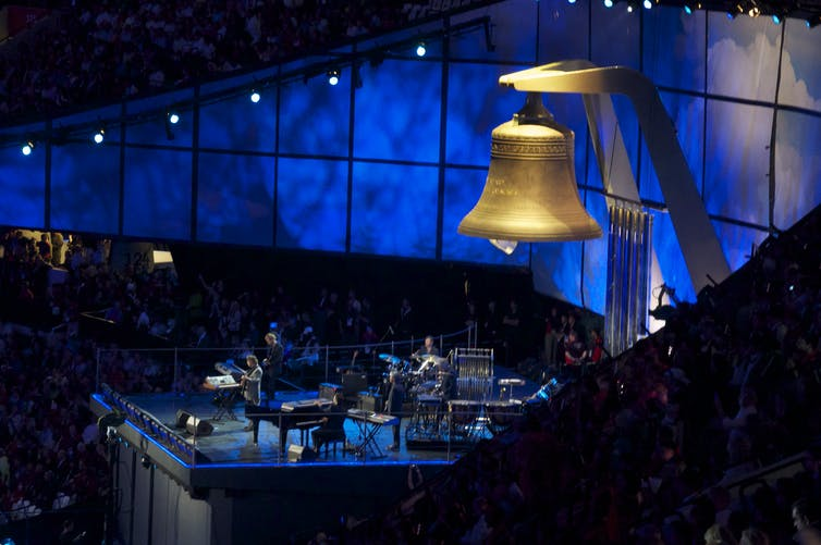 A giant bell hangs above a blue stage.