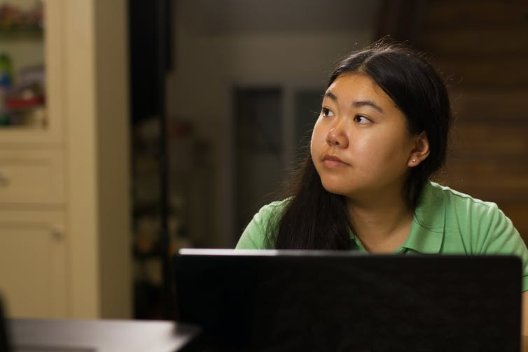 young woman looks away into the distance as she sits in front of a laptop