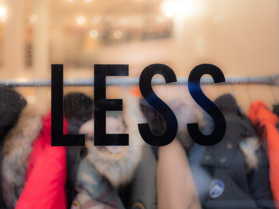 Clothes on a rack behind a window that says 'less'