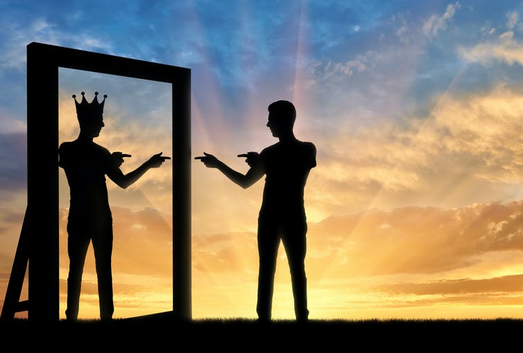 Silhouette of a man pointing at himself at the mirror, his reflection wearing a crown.