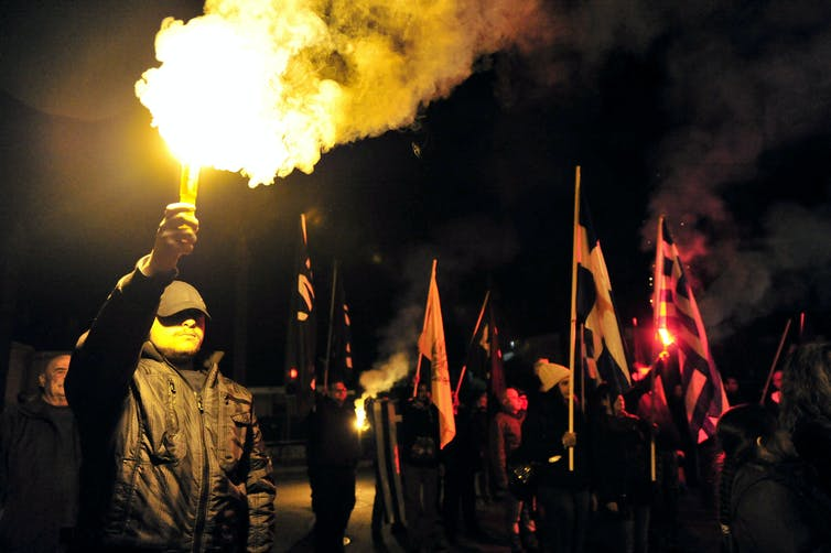 Protestors dressed in black wave flares at a night time gathering in Cyprus.
