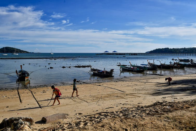 Moken children play on the beach, with small boats tied up in the shallows