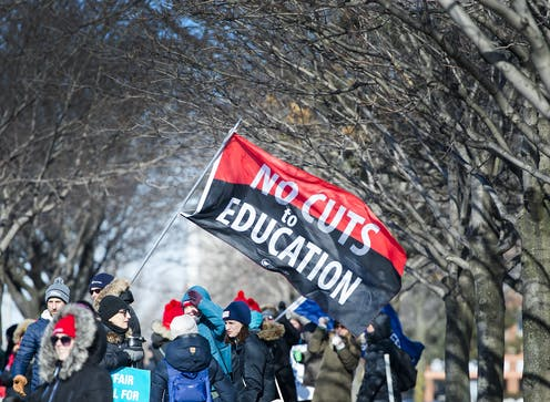 Teachers amass under trees during a one-day strike.