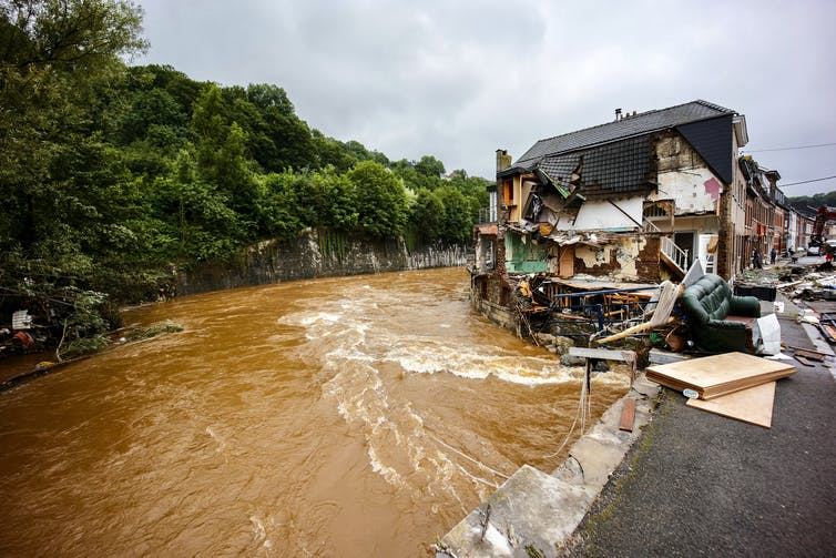 Muddy water water pours past a home where the side has been ripped open revealing the interior of rooms up to the second floor