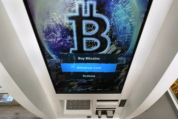 A Bitcoin ATM displays a bitcoin logo on the screen