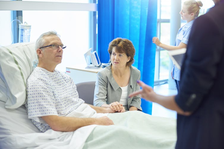 A patient in his hospital bed talks to his spouse and a doctor.