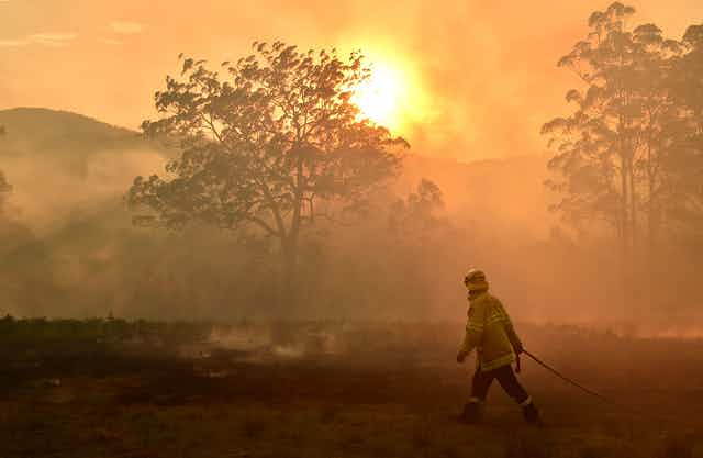 A wildland firefighter with a hose walks through a burned landscape with smoke filling the sky