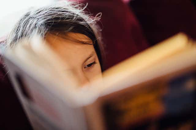 Close-up of young reader with book obscuring half their face