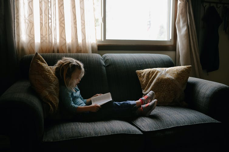 Young girl reading book on couch next to window