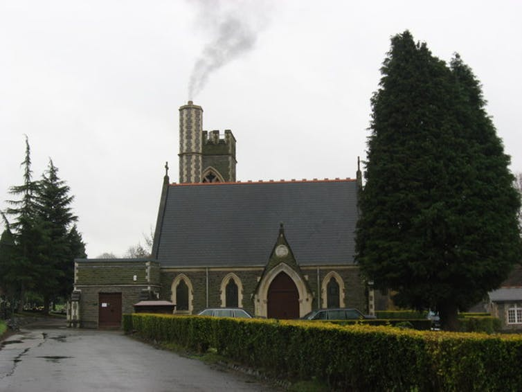 A church with crematorium behind, out of which smoke is issuing