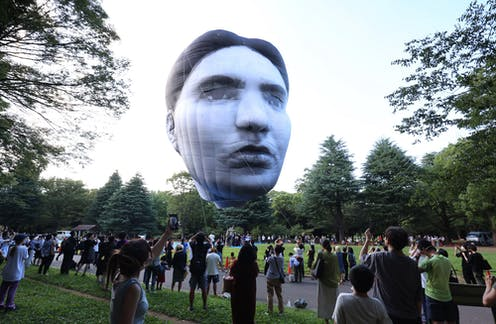 A giant inflatable head hovers over a crowd of spectators in a Tokyo park