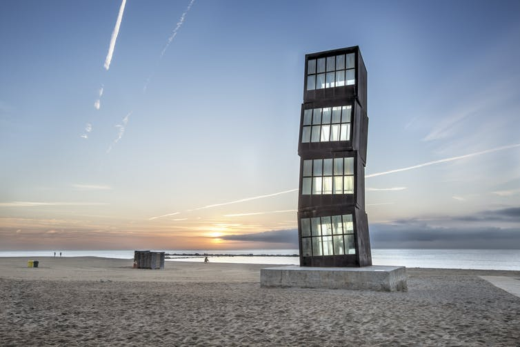 A large steel and glass sculpture on a beach in Barcelona