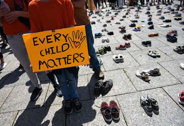 A child wearing an orange shirt holds a sign that reads 'every child matters' they are surrounded by hundreds of childrens shoes
