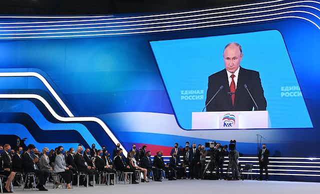 Putin's face is project on a large screen; people sit in chairs, wearing face masks, watching the screen in a large convention hall