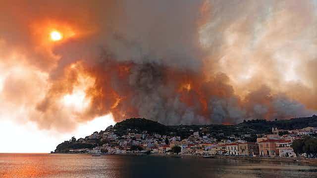 une épaisse fumée bloque le soleil au-dessus d'un village côtier