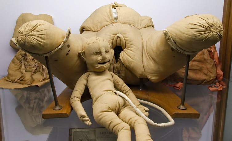 A dummy child attached to a model woman via an umbilical cord.