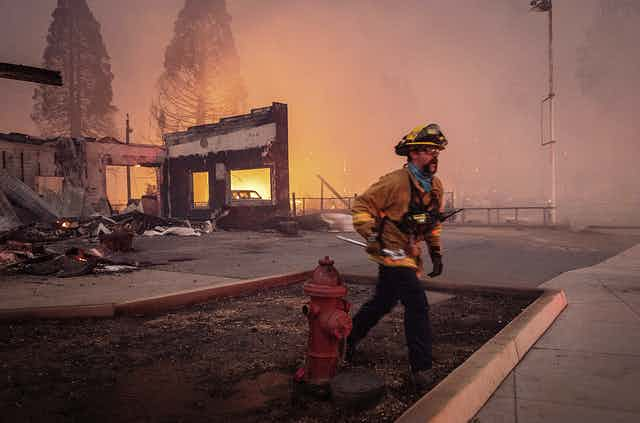 A firefighter in front of a destroyed building, smoke haze and fire in the background