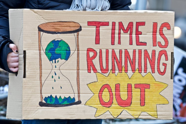 A home made protest placard showing the world inside an egg timer with the words 'time is running out'.