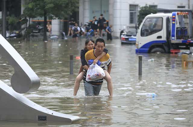 A man carries a woman through floodwaters in China