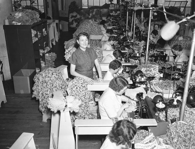 Uma grande sala está cheia de mulheres sentadas à mesa e usando máquinas de costura para fazer roupas, enquanto uma mulher está de pé, em 1937