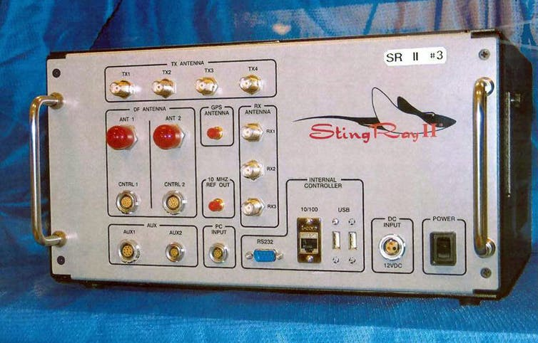 An electronic device with handles on either side of a front panel containing buttons and lights and a graphic representation of a stingray