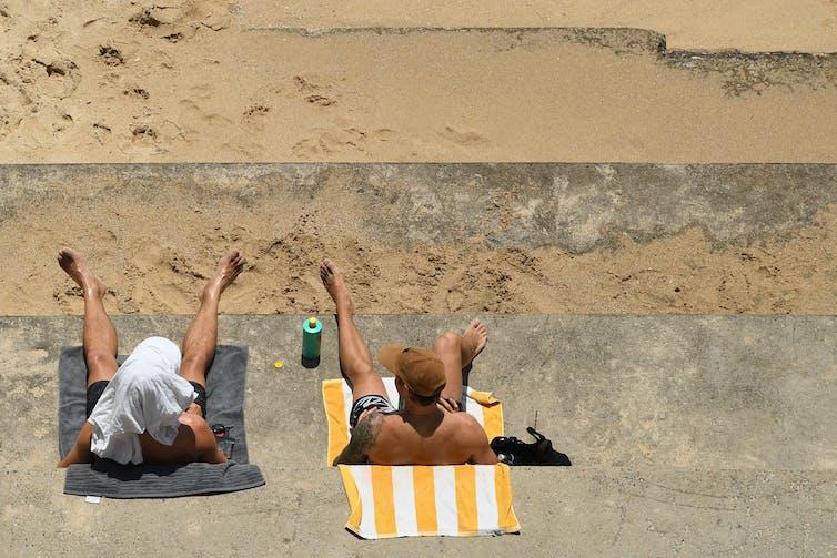 two men lie in sun