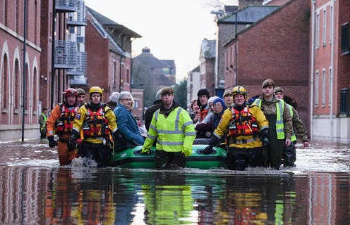 Rescue crews guide a large inflatable raft with several older residents seated inside through a flooded city street.