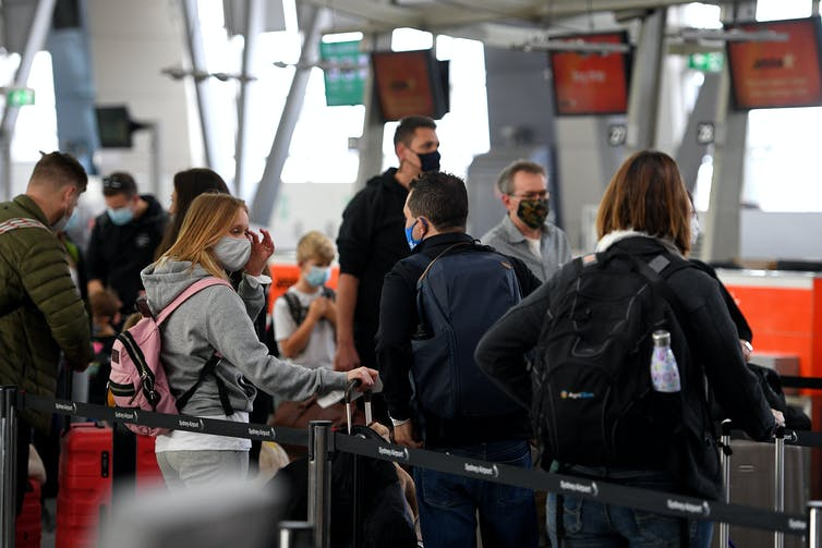 Passengers at Sydney airport line up to check package.