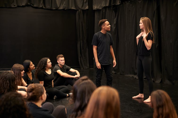 Students doing improvisation in drama class, wearing all black.