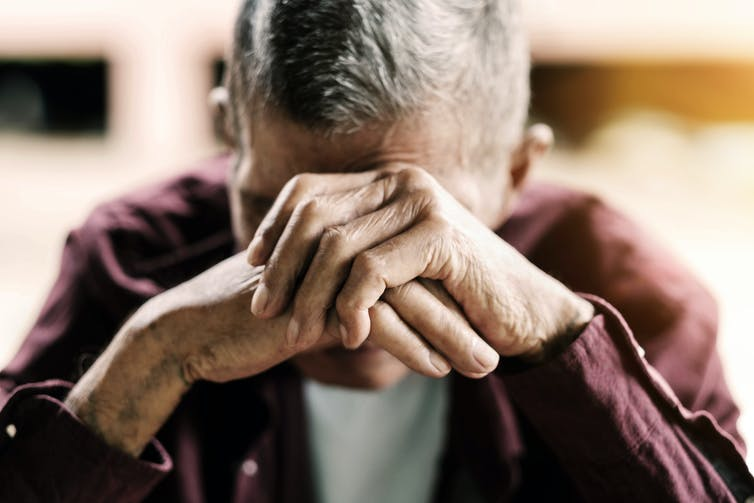 A man rests his head on his hands.