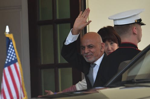 Ghani waves as he gets out of a car