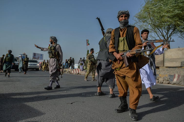 Fighters with guns stand on a road