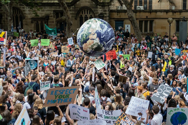 Youth strike demonstrators gather with signs and bounce an inflatable planet Earth.