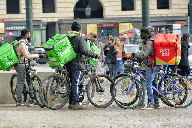 a group of cyclists with Uber eats and Just Eat delivery backpacks