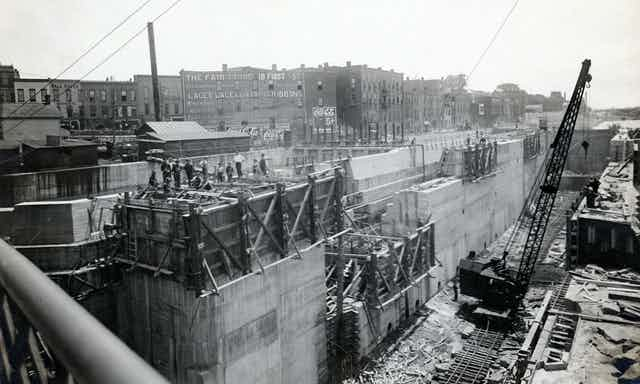 A black and white photo of a construction site, digging a large ditch and working on it with a crane