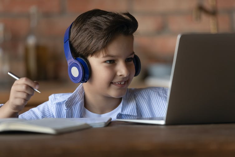 Young boy prepares to write as he talks with someone on his laptop