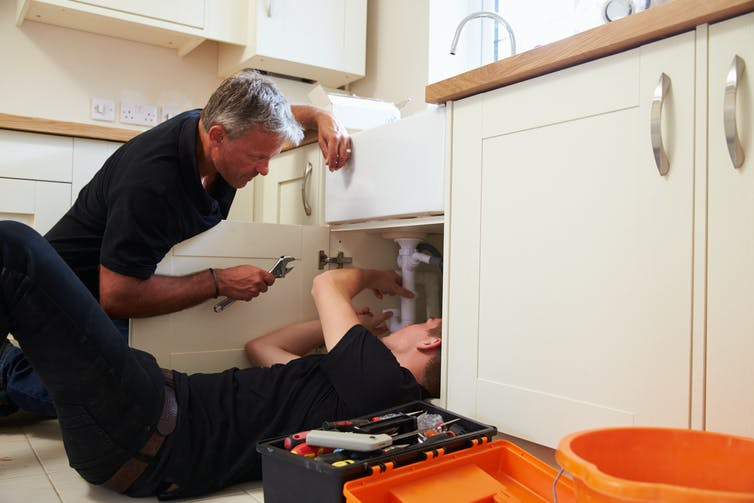 Plumber showing a young apprentice how to fix a sink.