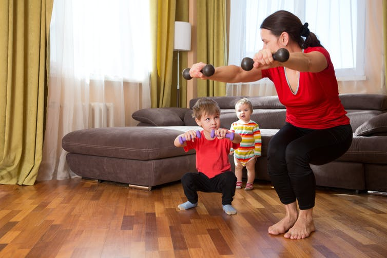 A woman does exercise at home with kids.