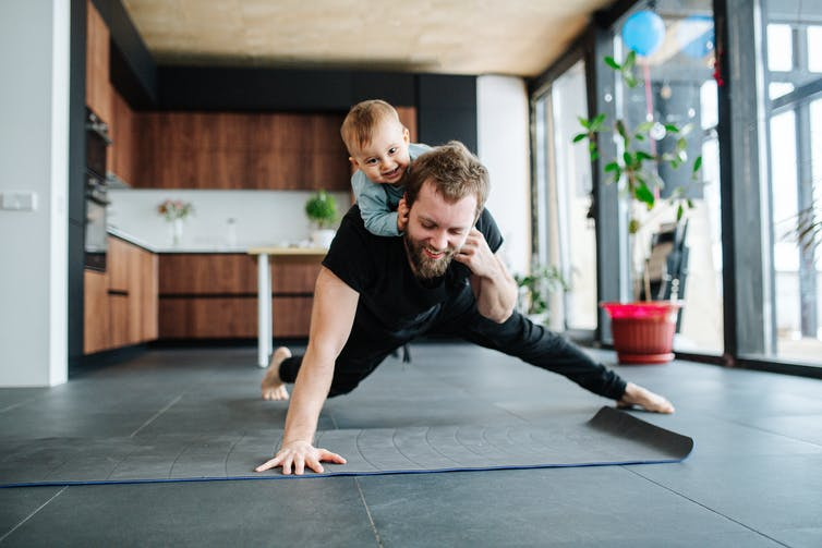 A man does a push-up with a kid on his back.