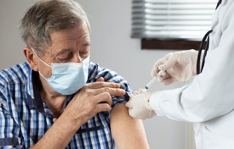An elderly man in a mask being vaccinated