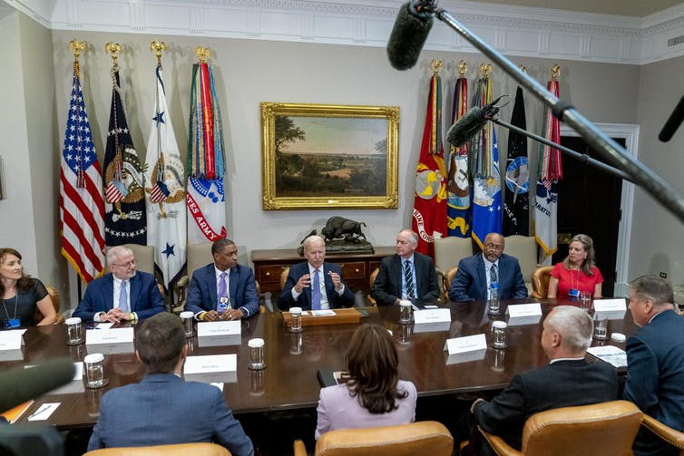 Men and women in business suits sit around a large table.