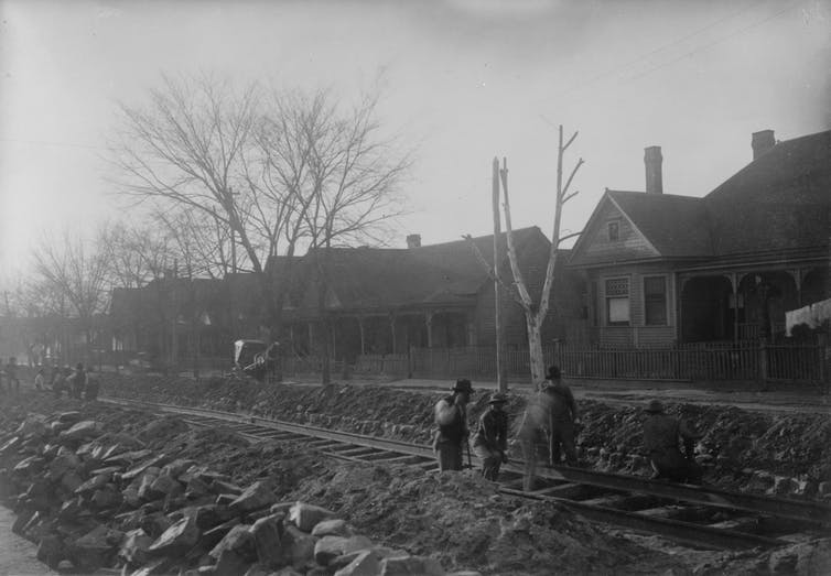 A black and white photo of people working to build a railroad.