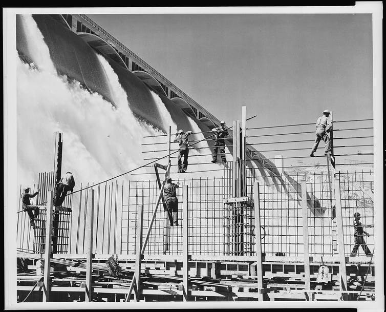 A black and white image of people working to build a large hydroelectric dam