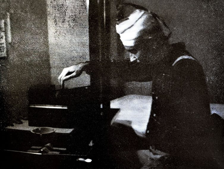Black and white grainy photograph of a person pressing a button.