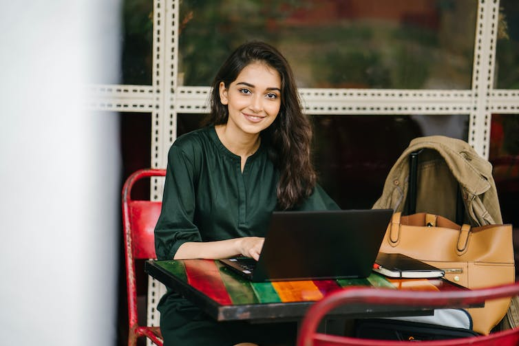 A smiling woman sits behind a laptop.