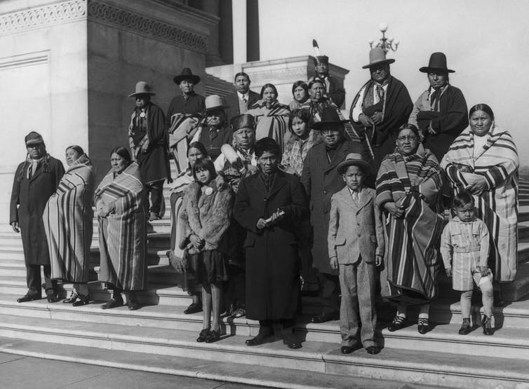 Members of the Osage Nation from Oklahoma stand on the steps of the Capitol in Washington D.C.