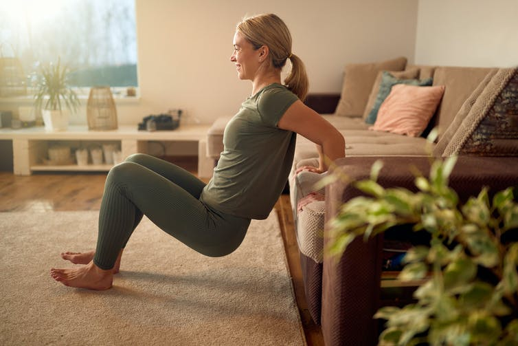 A woman does tricep dips at home.